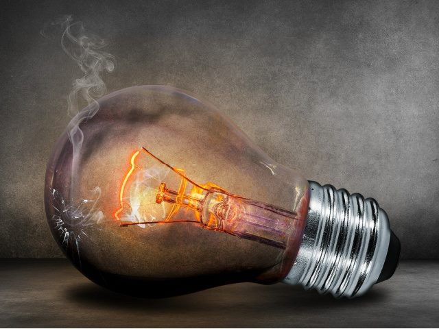 incandescent light bulb with a crack in it on a gray background