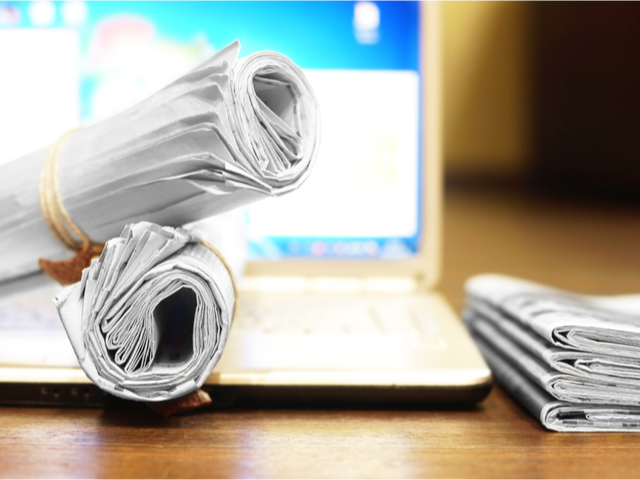 Rolled up newspapers on a laptop computer - news concept