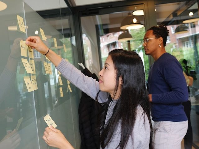 two people adding post it notes to a physical kanban board