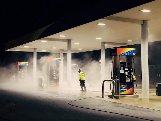 employee hosing down a gas station  at night