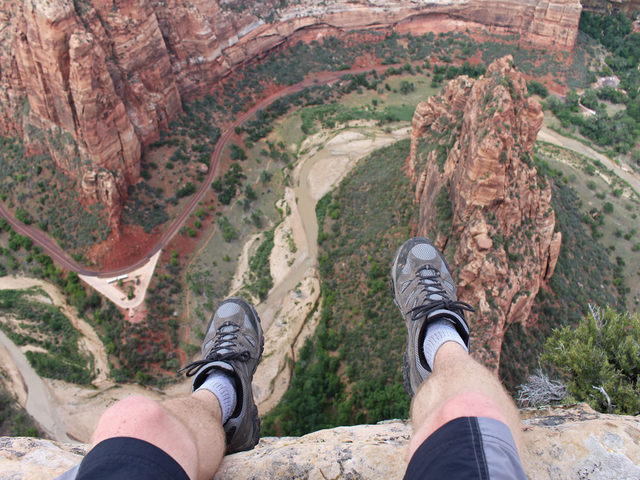 First person perspective shot from a hiker sitting at the edge of a cliff