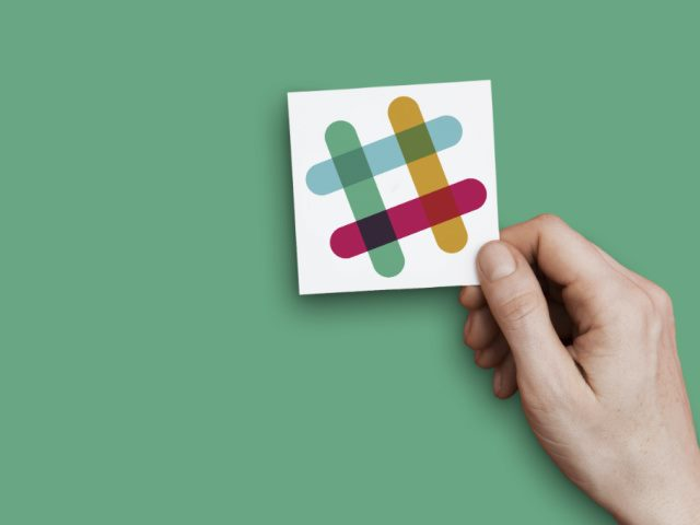 hand holding a card with the Slack logo against a green background