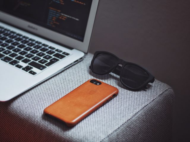 orange smartphone laptop computer and sunglasses on a gray background