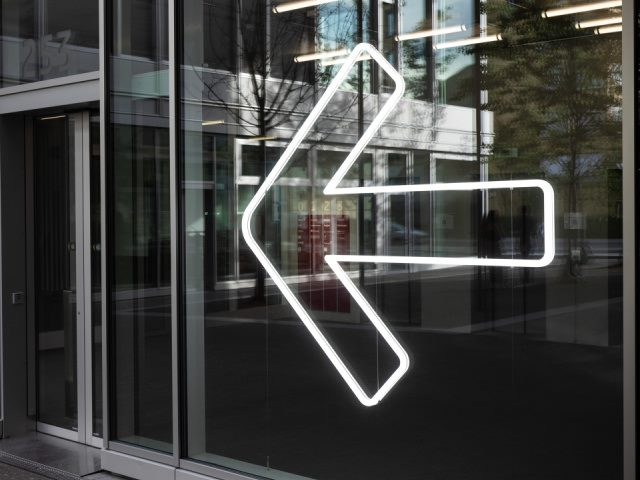 white neon arrow pointing the way to a glass door