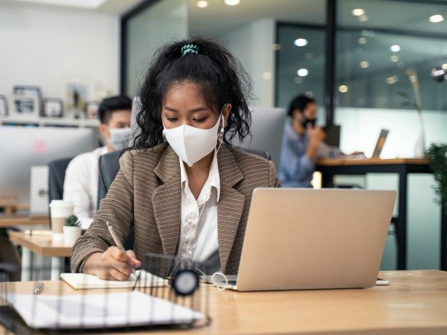 Businesswoman wearing mask working on computer in office.