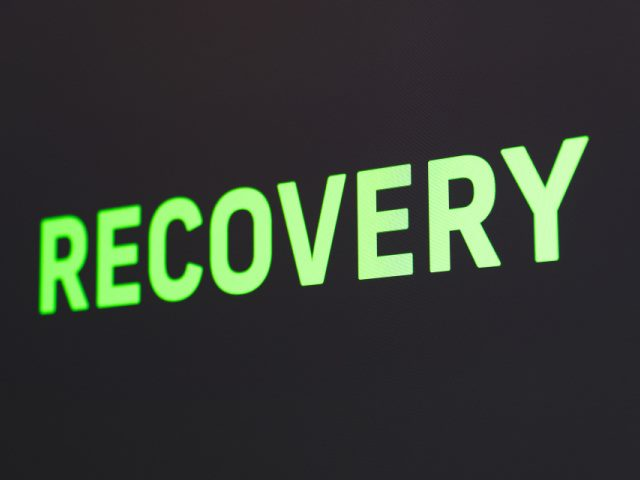 recovery spelled out in illuminated green text on a black background