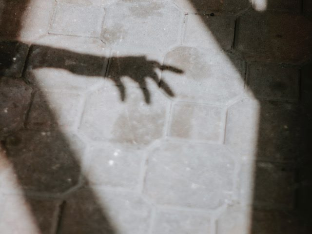 the shadow  of  an arm stretching  out