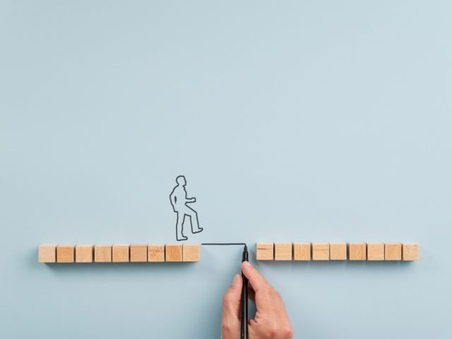 hand drawing of a figure crossing a gap between two wooden blocks