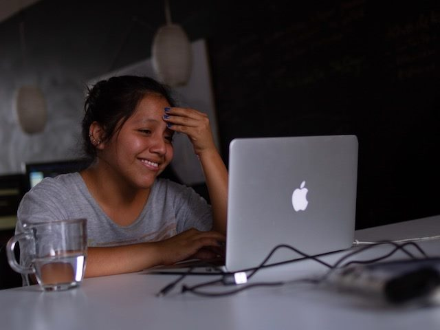 smiling woman looking at her laptop, leaning her head in her hand