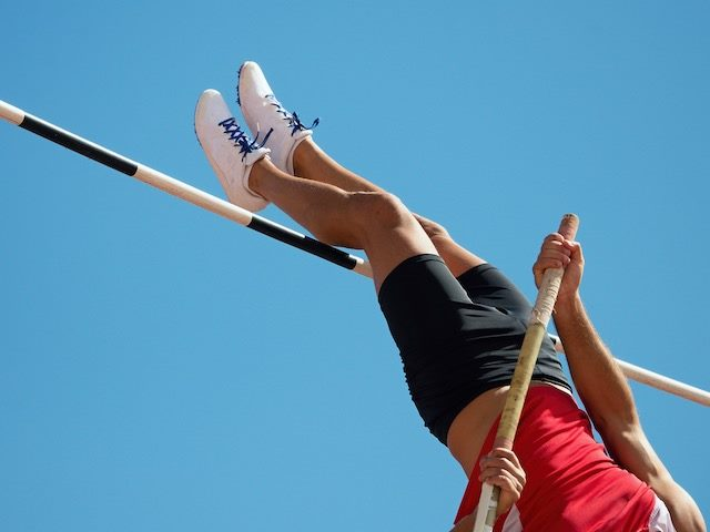 person doing the pole vault, just going over the high bar, blue sky behind