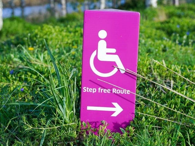 pink and white disability access sign on green grass