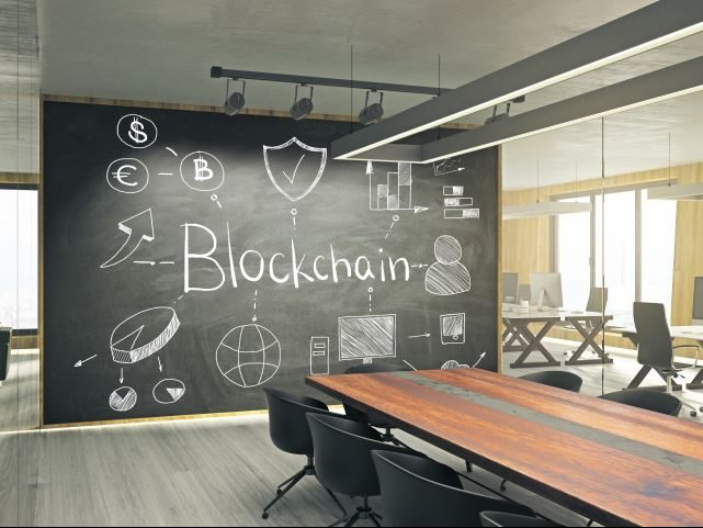 An open office setting with a large chalkboard in the middle. The chalkboard says blockchain - Blockchain in the workplace concept