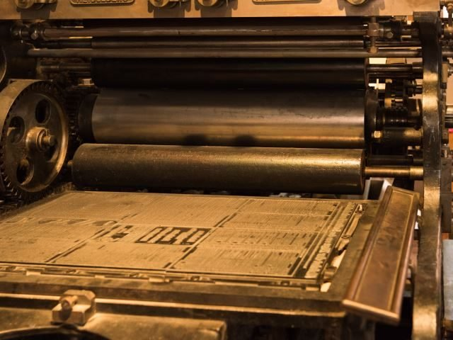 An antique newspaper printing press, printing the daily news - Newsbyte concept