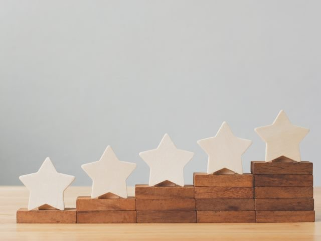 five wooden stars on a table in stair step fashion