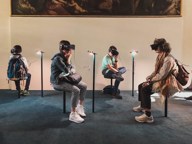people sitting in an art gallery wearing VR goggles