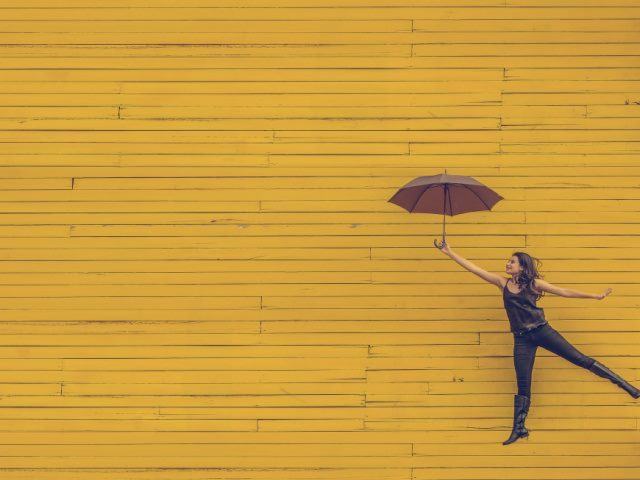 woman holding an umbrella and leaping against a yellow background