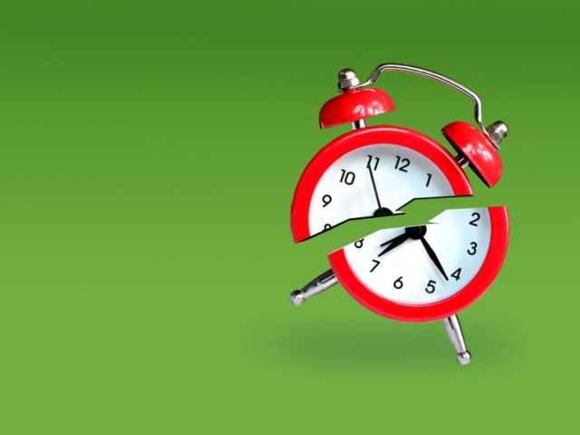 red alarm clock broken in half against a green background