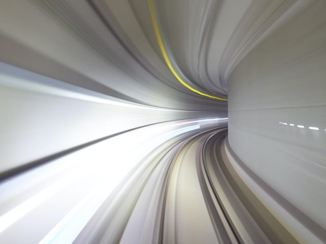 time lapse photo of a gray subway tunnel with yellow and white lights