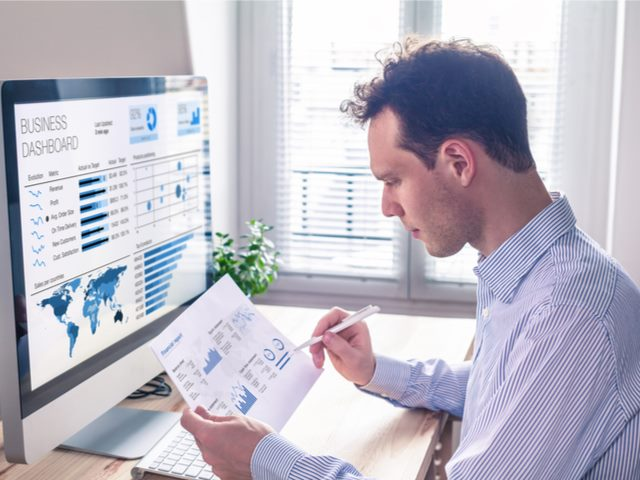 Man studying analytics and KPIs at his desktop PC