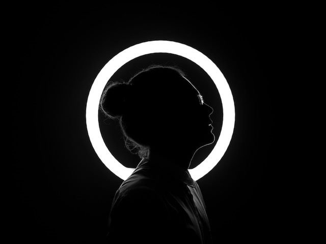person in silhouette standing in front  of  a  circular neon light