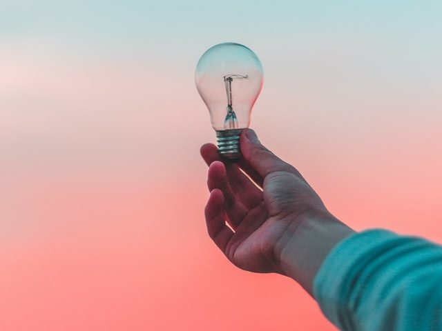 person holding lightbulb against a blue and pink sky