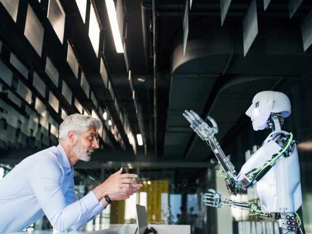 Mature businessman or a scientist with gray hair with a robot/artificial intelligence (AI)