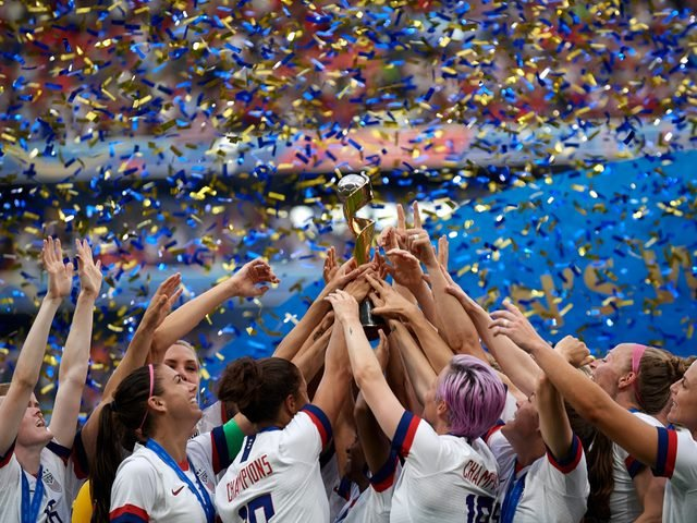 US women's soccer players celebrating together after winning a medal.