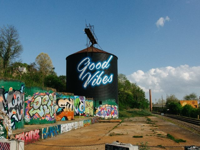 black silo alongside railroad tracks with Good Vibes message painted in white