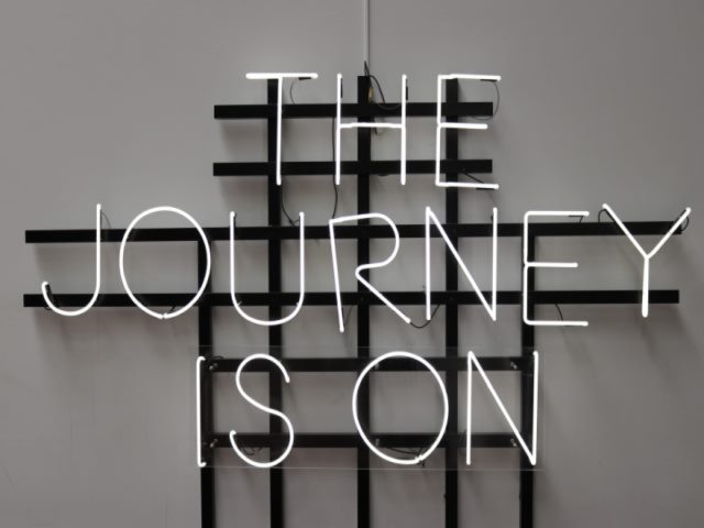 White neon sign on gray background with message saying The Journey Is On