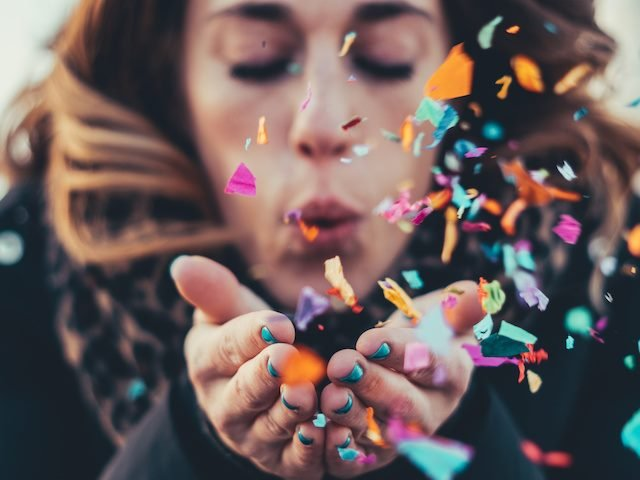 woman blowing colorful confetti out of her hands