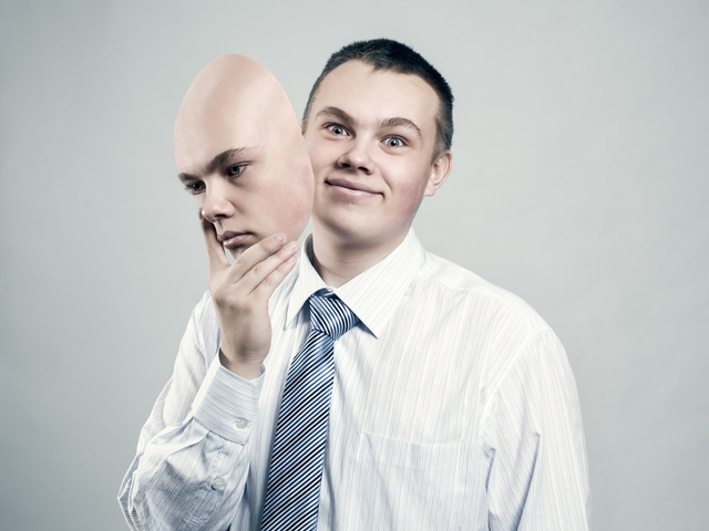 A businessman removes the mask from the face of a bad mood