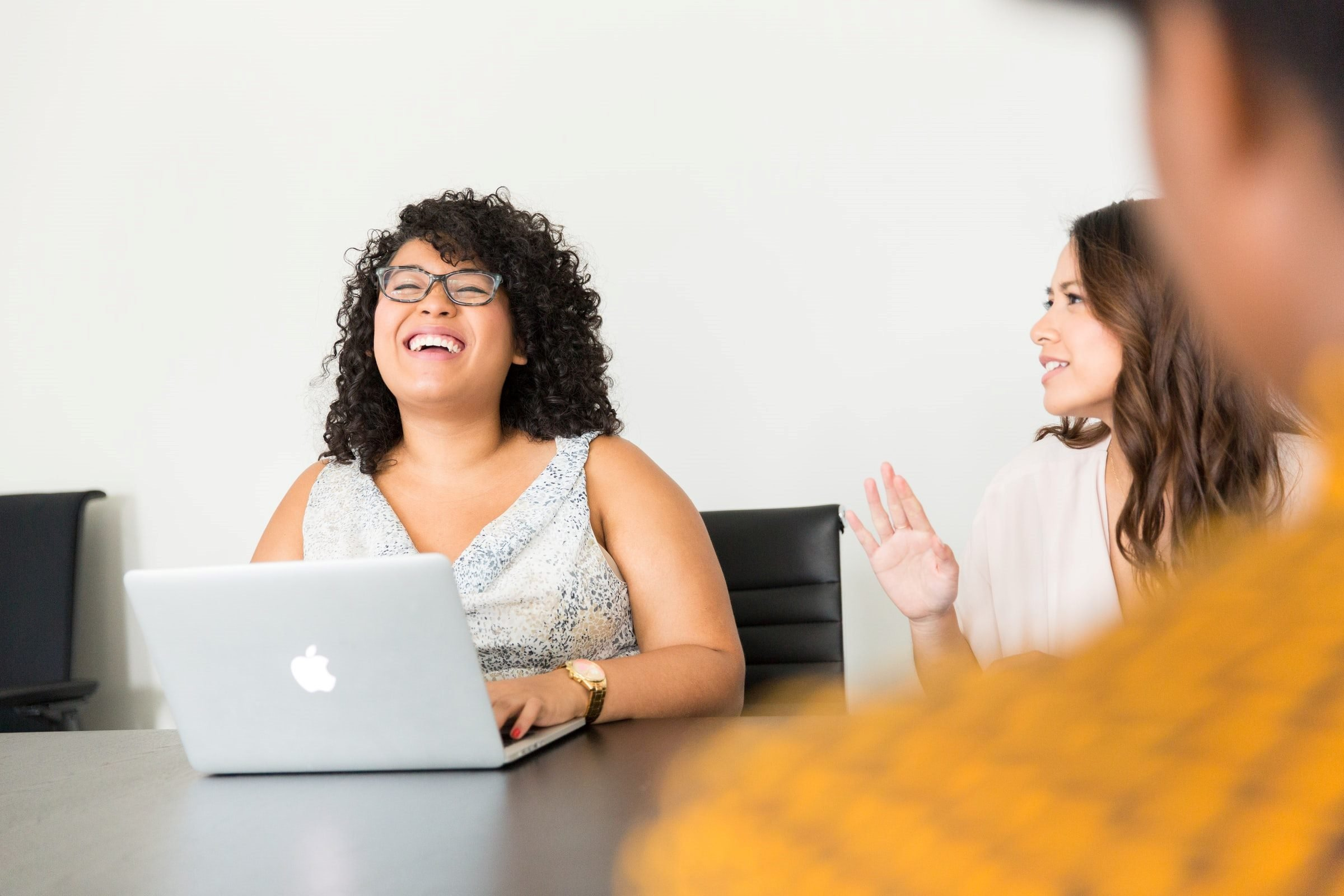 women in conference room with laptop