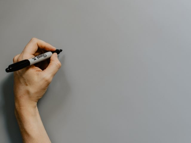 person holding a black permanent marker over a gray background