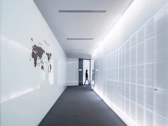 stylish hallway with world map on one side, person walking through in the background