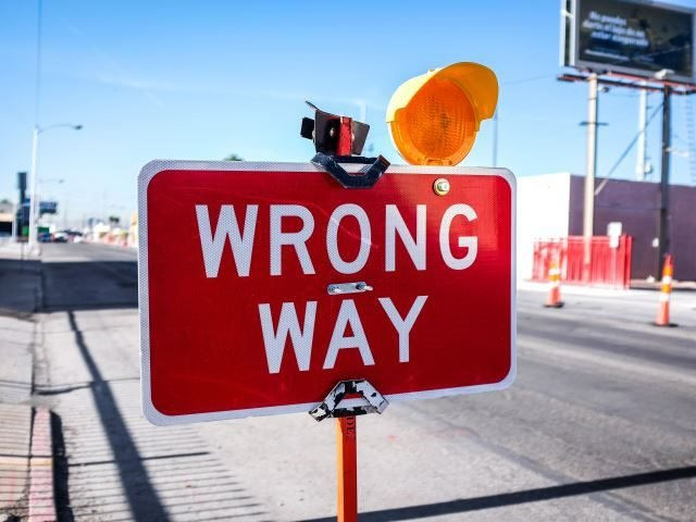 A wrong way sign on the road way before construction - negative impact concept