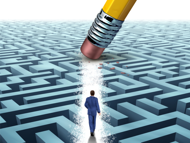 A businessman walking through a complicated maze opened up by a pencil eraser - optimization concept