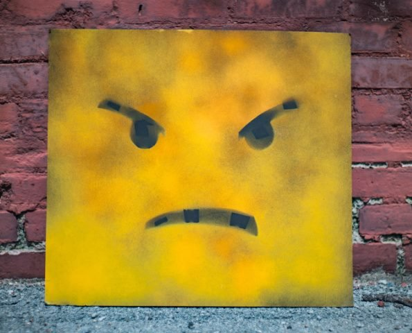 mad face painted in yellow and black frame in front of a red brick wall