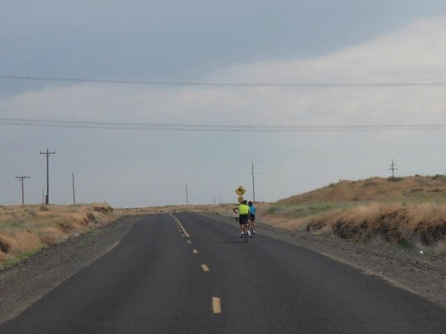 Two bikers ride forward in an otherwise empty road.