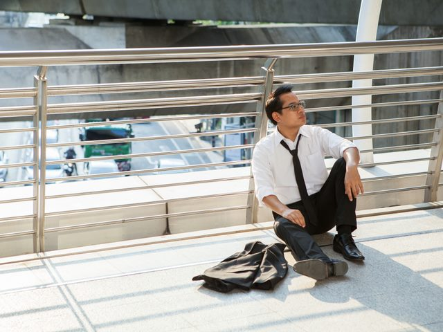 A man in a business suit sitting on the ground.
