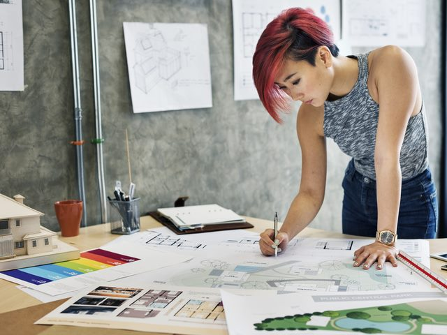 a woman working on design charts.