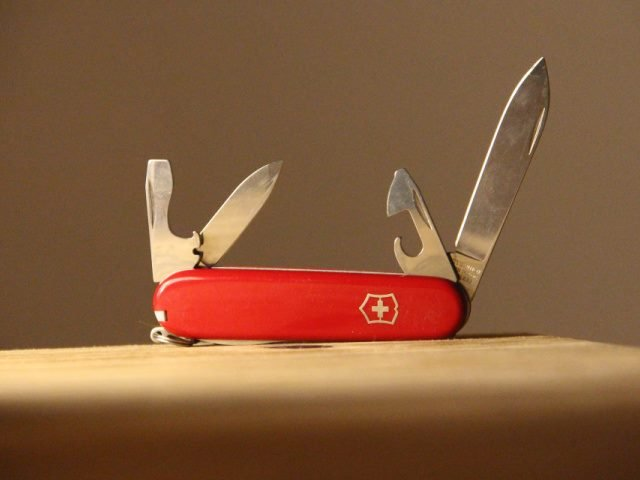 open swiss army knife on a wooden table