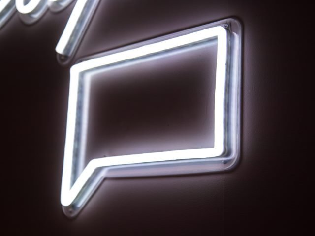 white neon message sign on a black wall