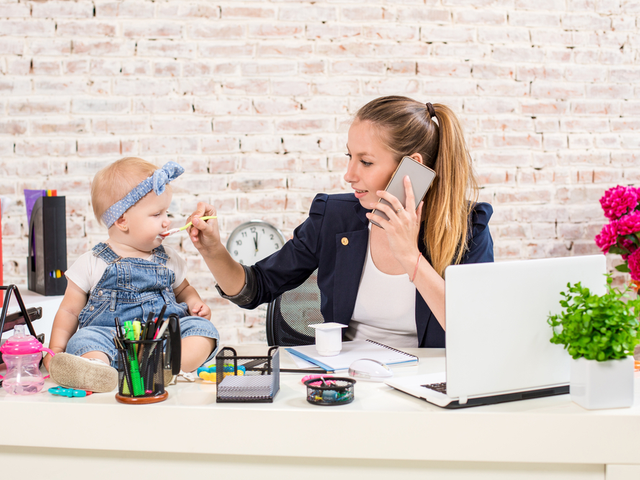 A businesswoman feeding her child is making a phone call at her work desk