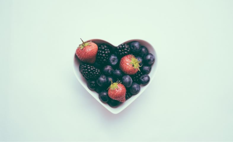 a heart shaped bowl of blueberries and strawberries on a light background