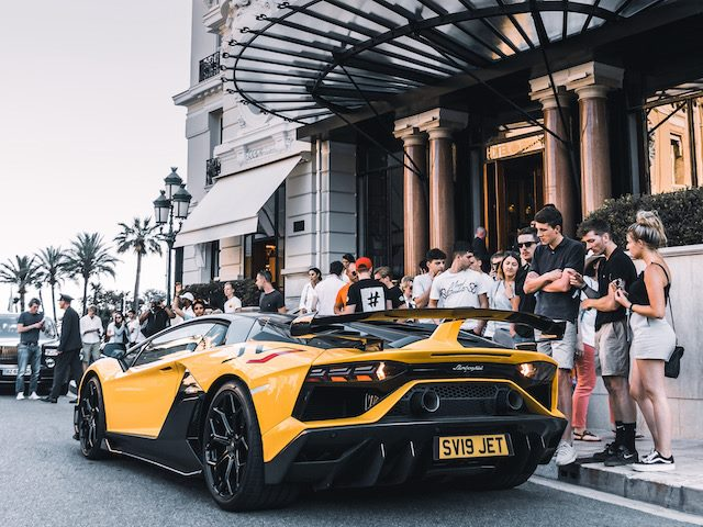 lamborghini parked in front of a hotel with a crowd surrounding it