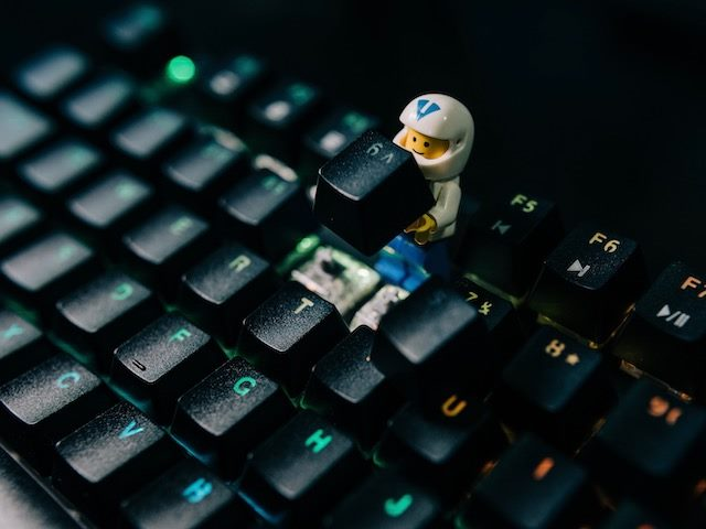 lego figurine working on a computer keyboard, replacing a key