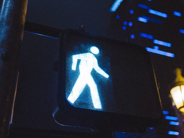 black and white pedestrian walking sign at night