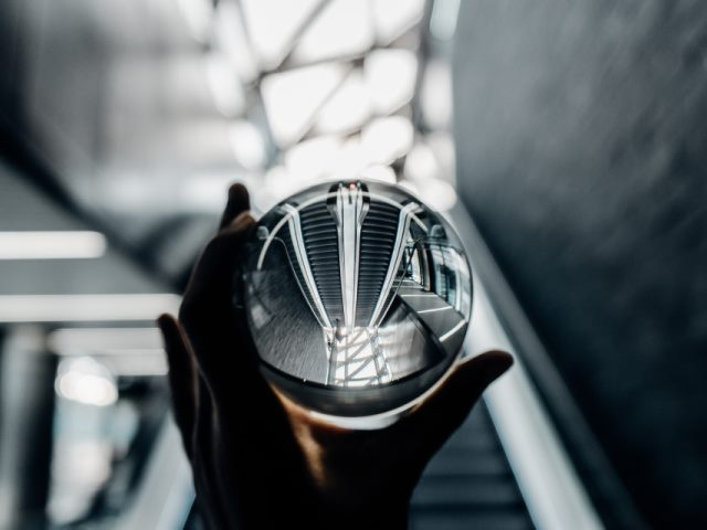 person holding clear glass ball with an escalator in the background