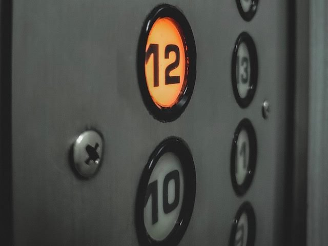elevator panel, button lit up to go up to 12th floor