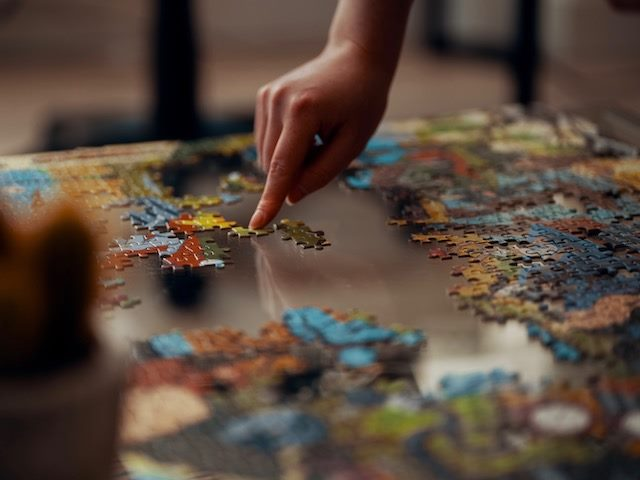 unfinished jigsaw puzzle with a person's finger holding down one piece